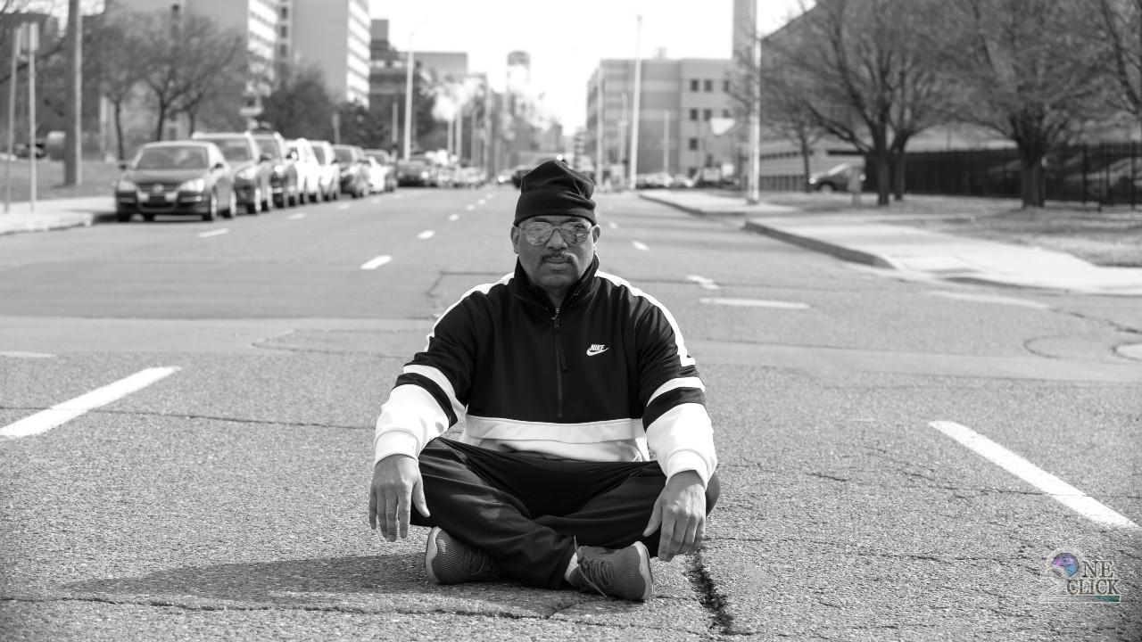 Eddie Fowlkes sitting in street black and white