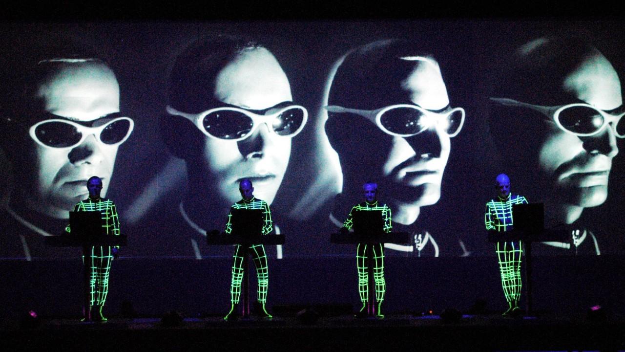 Kraftwerk neon jumpsuits faces screen